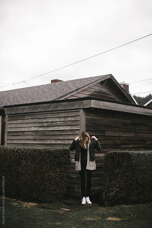 young woman standing in front of beach house on windy day by Nicole Mason for Stocksy United