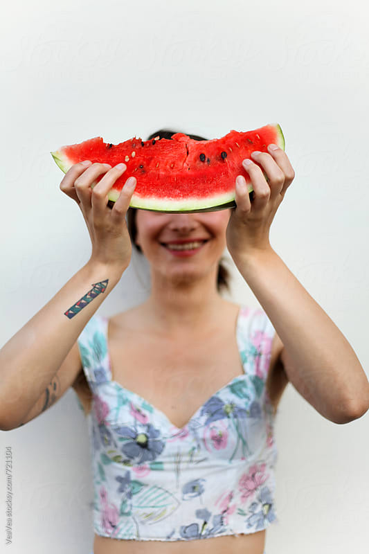 Woman holding a slice of watermelon in front of her face  by Marija Mandic for Stocksy United