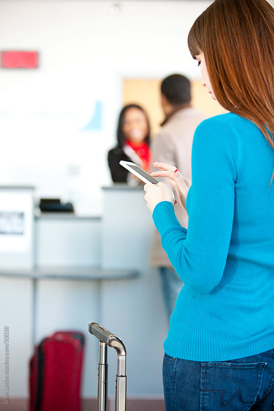Airport: Woman Texting While in Line at Ticket Counter by Sean Locke for Stocksy United