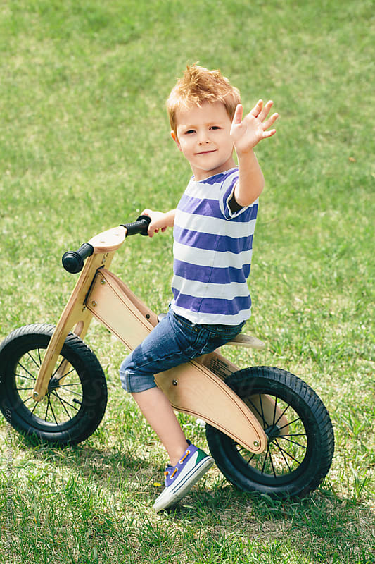 Young boy waving and riding a bike on the grass by Ania Boniecka for Stocksy United