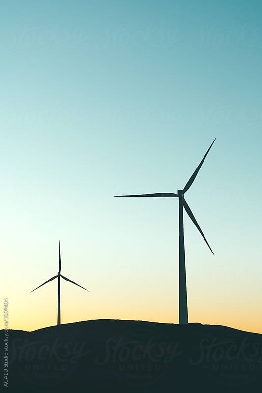 Pair of windmills at sunset by ACALU Studio for Stocksy United