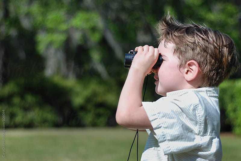 boy  watches for wildlife with binoculars by Cara Dolan for Stocksy United