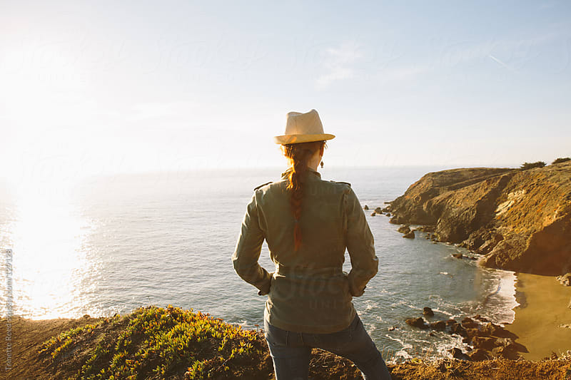 Woman in nature looking at view of pacific ocean by Trinette Reed for Stocksy United