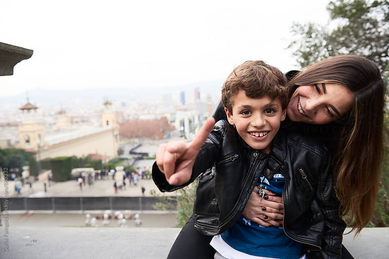 Sister and brother hugging and smiling. Boy showing peace sign at camera by Guille Faingold for Stocksy United