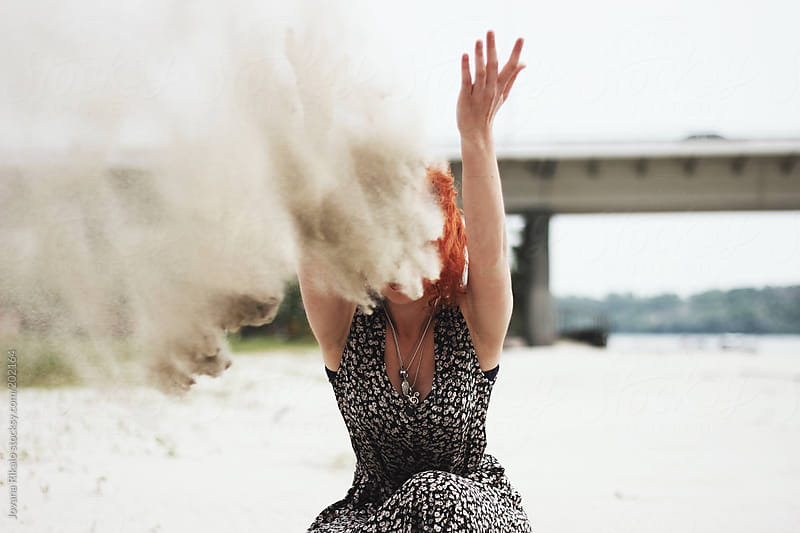 Young ginger woman throwing sand in the air by Jovana Rikalo for Stocksy United