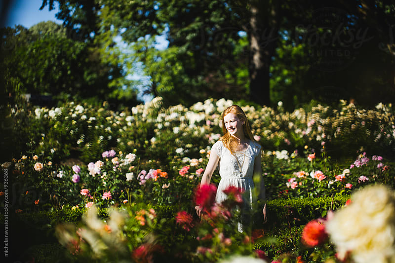 Redhead young woman enjoying her time in a garden of roses by michela ravasio for Stocksy United