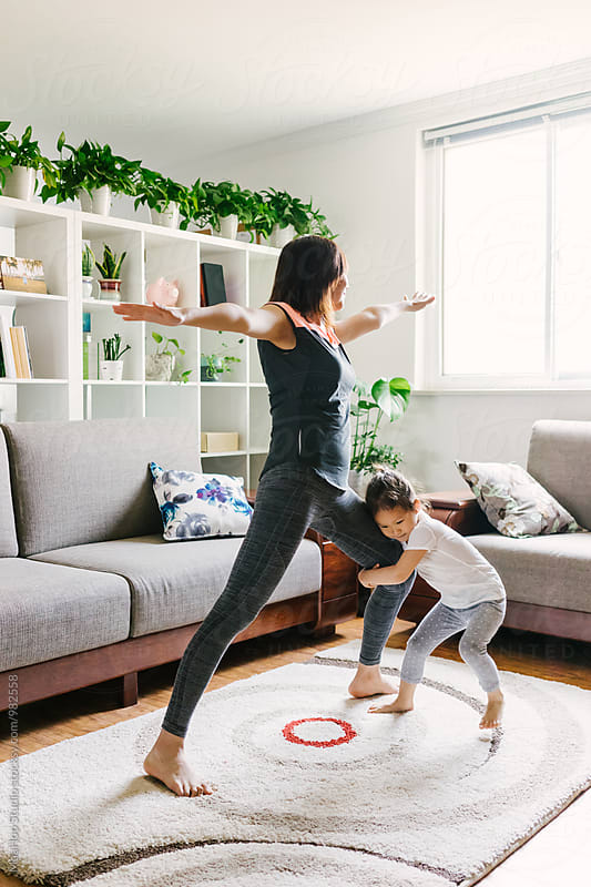 Adorable little girl doing yoga with her mother by Maa Hoo for Stocksy United