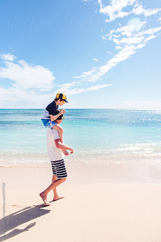 Boy having a shoulder ride during a walk at the beach on a summer's day by Angela Lumsden for Stocksy United