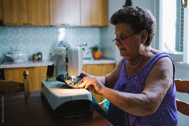 Senior woman is sewing at home by GIC for Stocksy United