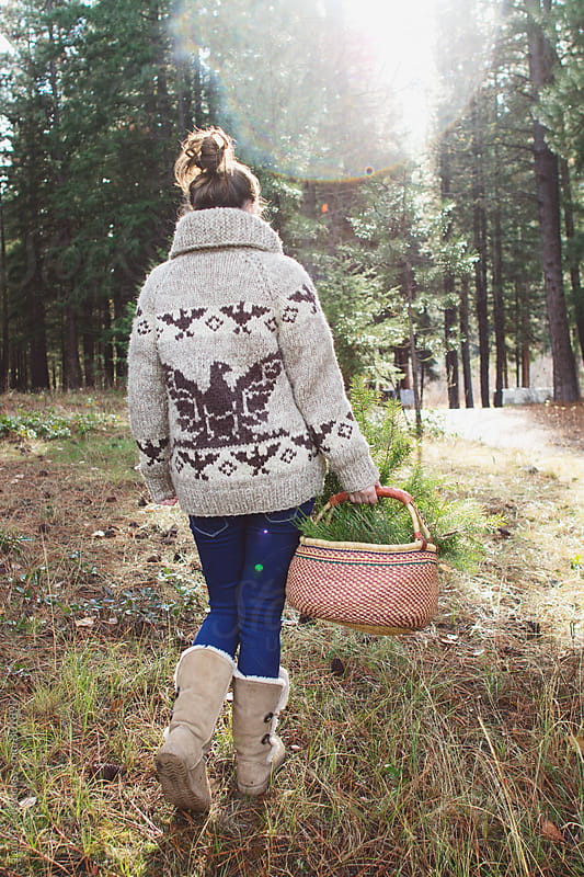 young woman walking in forest with basket of greenery by Tana Teel for Stocksy United