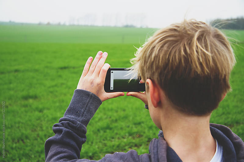 Boy taking a photograph with his smartphone by Helen Rushbrook for Stocksy United