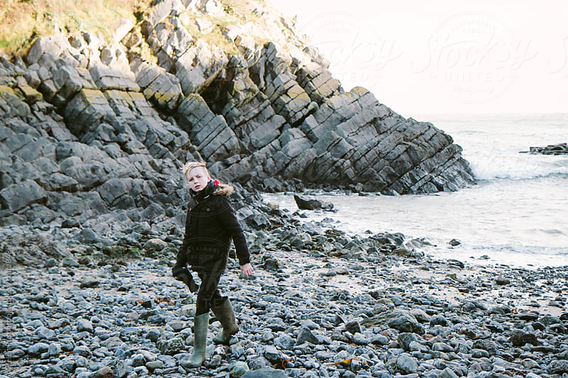 Teenage boy walking on a rocky foreshore  by Helen Rushbrook for Stocksy United