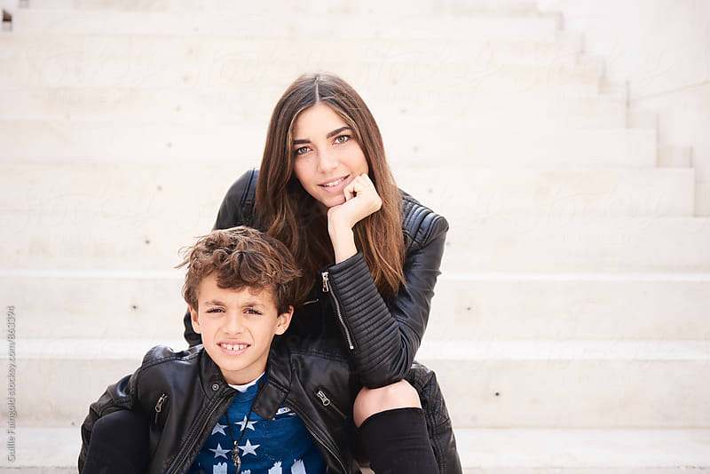 Younger brother and sister sitting on steps  by Guille Faingold for Stocksy United