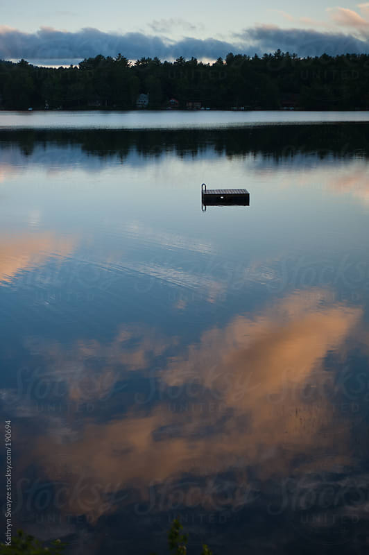 Clouds at sunset are reflected by lake water, surrounding a swimmer's raft by Kathryn Swayze for Stocksy United
