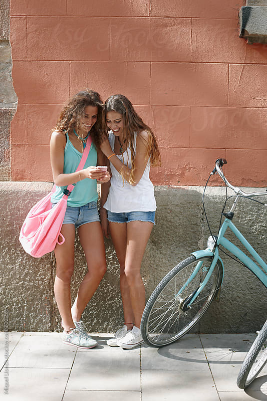 Two young girls with bikes checking the phone in a city by Miquel Llonch for Stocksy United