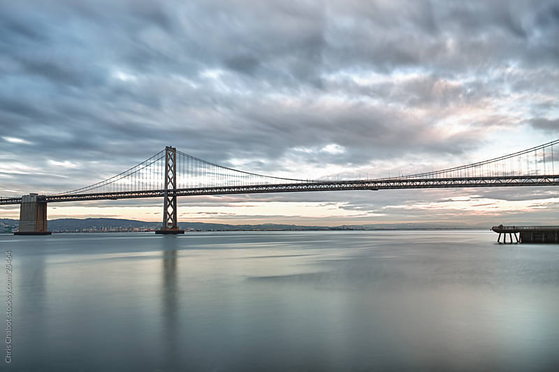 Bay Bridge during a storming evening by Chris Chabot for Stocksy United