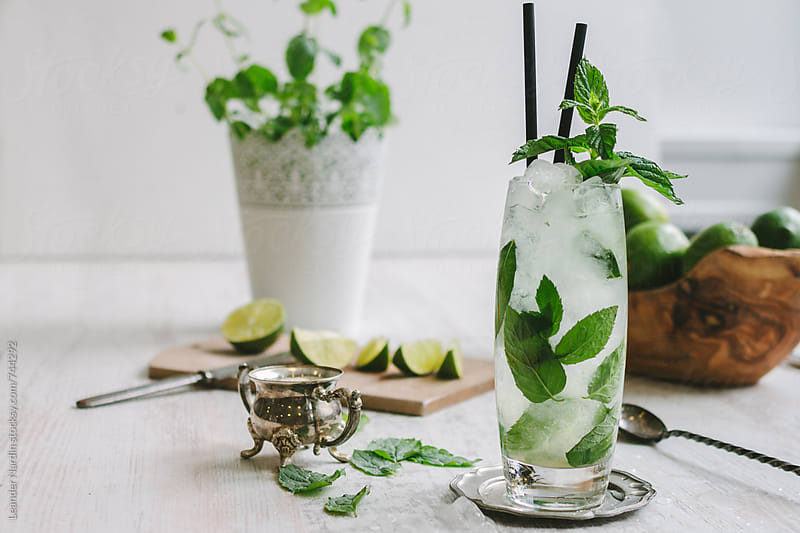 mojito cocktail with fresh mint garnish on a white table with ingredients by Leander Nardin for Stocksy United