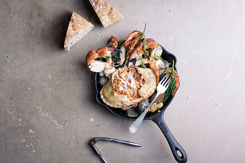 Dressed crab served with crusty bread.Crab in a skillet. by Darren Muir for Stocksy United