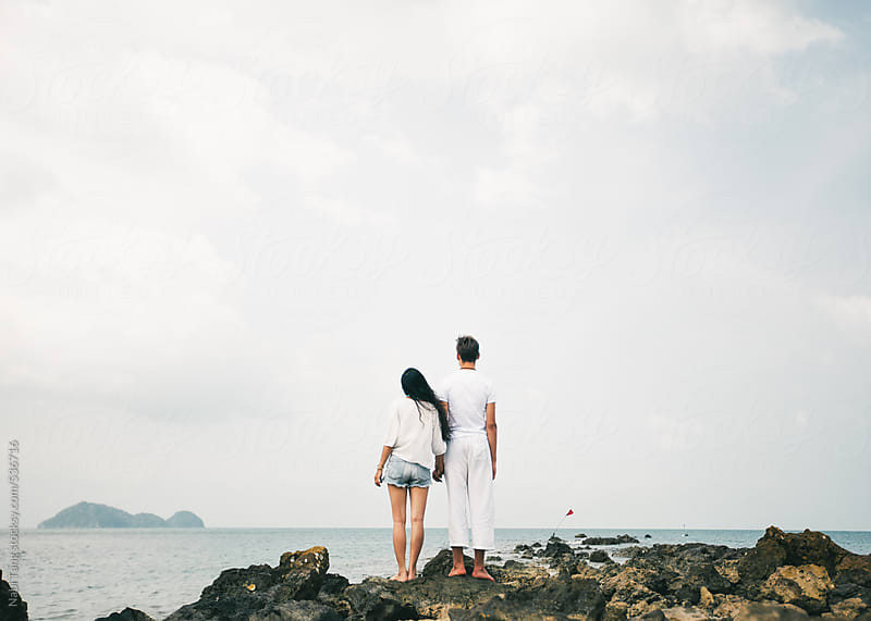 Couple on the rock looking at the sea by Nabi Tang for Stocksy United
