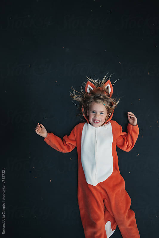 Cute girl in fox costume lying on trampoline by Rob and Julia Campbell for Stocksy United