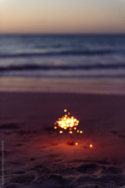 Blurred image of sparklers in the sand at the beach after sunset by Angela Lumsden for Stocksy United