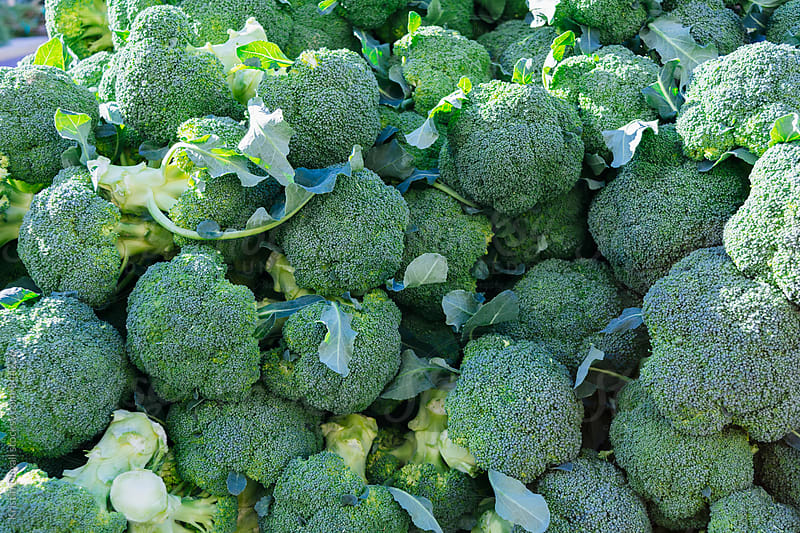 Fresh broccoli at market by Kristin Duvall for Stocksy United