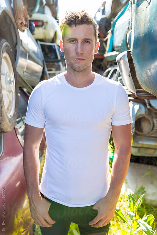 Young man standing between stacks of wrecked cars by Ben Ryan for Stocksy United