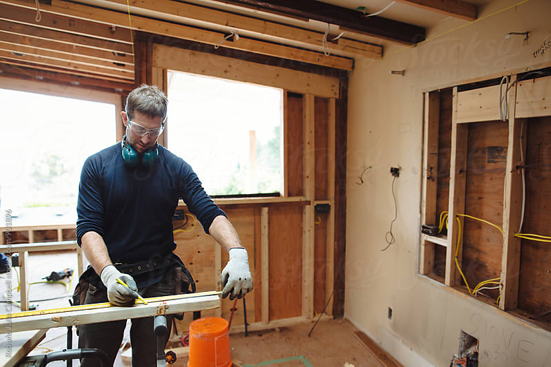 Carpenter measuring two by four - 2X4- wood inside  by Rob and Julia Campbell for Stocksy United