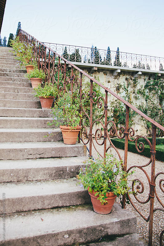 Potted plants adorning a stone staircase with iron railing at a Tuscan villa by Sarah Lalone for Stocksy United
