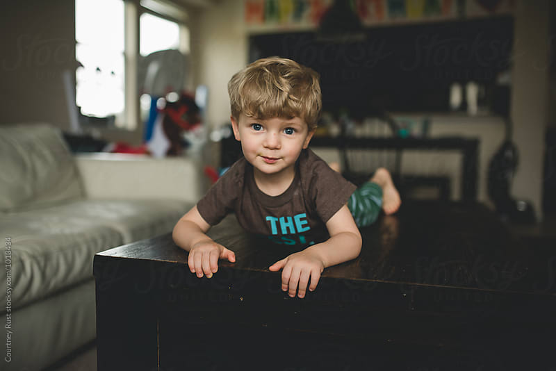 Toddler boy laying on coffee table by Courtney Rust for Stocksy United