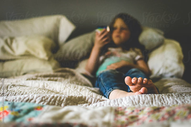 Little girl sitting on bed with an electronic device by Lindsay Crandall for Stocksy United