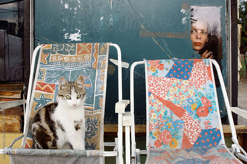 Girl is peeking through the little window ,cat sitting on colorful chair in front by Marija Anicic for Stocksy United