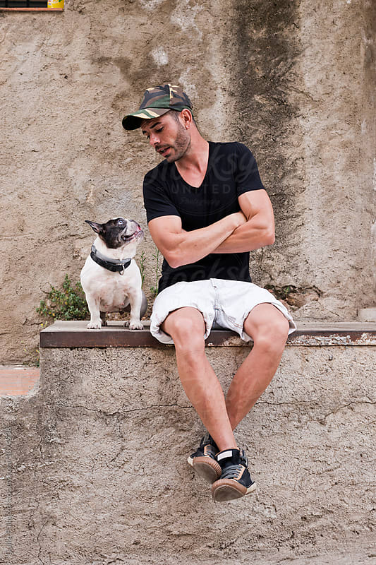 bearded man with arms crossed talking to his black and white dog by Guille Faingold for Stocksy United