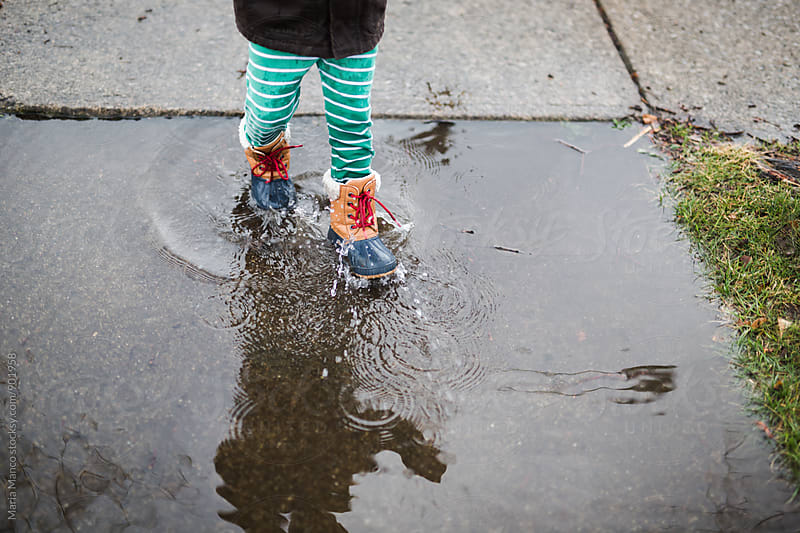Child walking through a rain puddle in boots by Maria Manco for Stocksy United