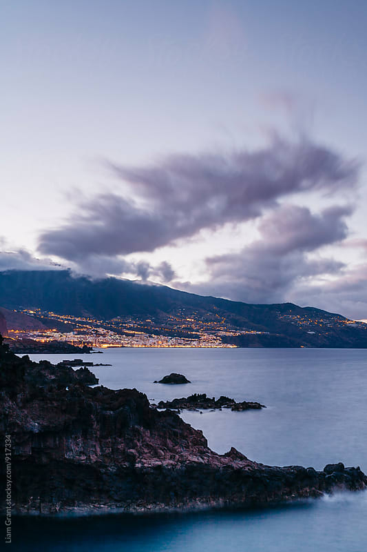Volcanic coastline and lights of Santa Cruz at twilight. La Palma, Canary Islands. by Liam Grant for Stocksy United