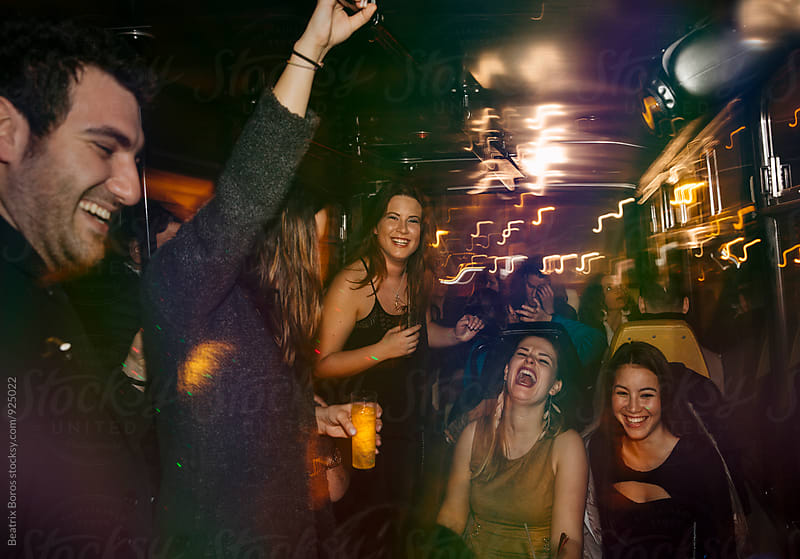 Young crowd of people laughing together in a club by Beatrix Boros for Stocksy United