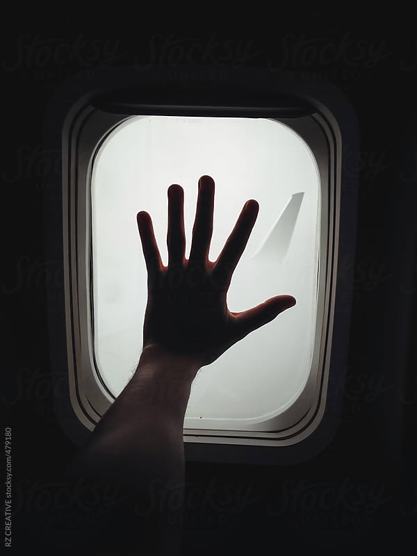 Hand against the window of a plane captured with mobile phone. by RZ CREATIVE for Stocksy United