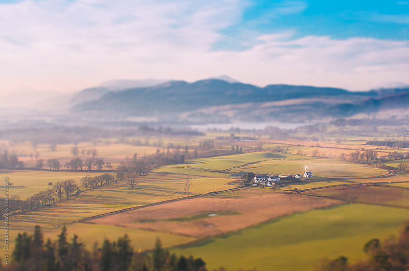 An aerial view of Scottish farm surrounded by fields, mountains, and countryside. by Andy Campbell for Stocksy United