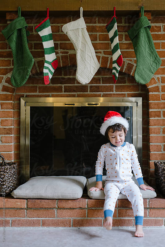 boy in pajamas and Santa hat sits in front of fireplace with stockings by Tara Romasanta for Stocksy United