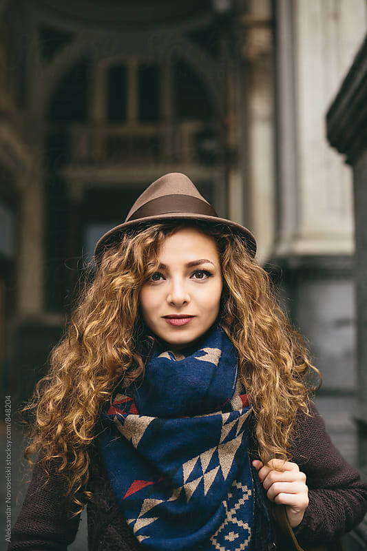 Portrait of beautiful woman with hat and curly hair, in urban environment by Aleksandar Novoselski for Stocksy United