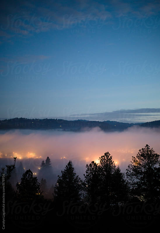 Fog suspended in the valley of a small town by Carolyn Lagattuta for Stocksy United