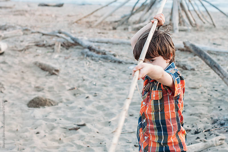 Boy playing with a stick on the beach by Beatrix Boros for Stocksy United