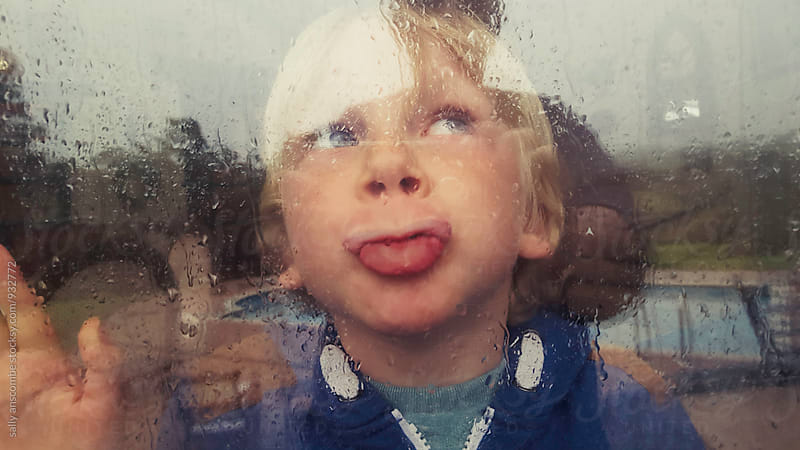 Child looking out of the window on a rainy day by sally anscombe for Stocksy United