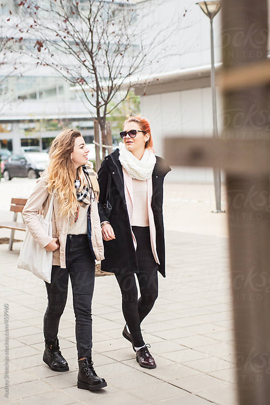 Two friends enjoy in chat during walk. by Audrey Shtecinjo for Stocksy United