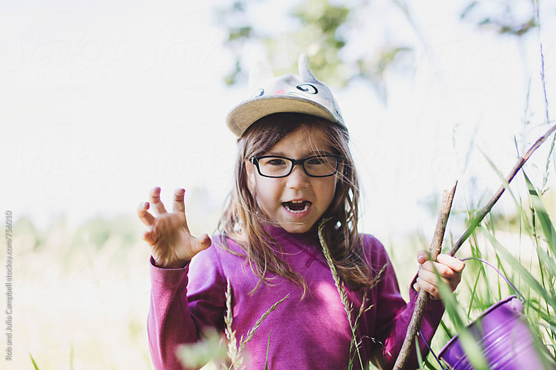 Cute girl having fun in nature - growl by Rob and Julia Campbell for Stocksy United
