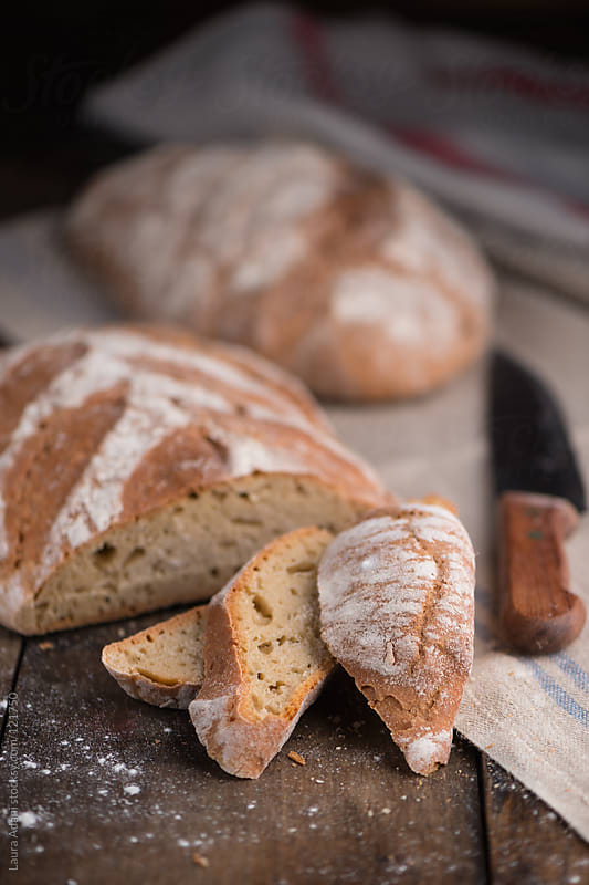 a loaf of bread cut into slices by Laura Adani for Stocksy United