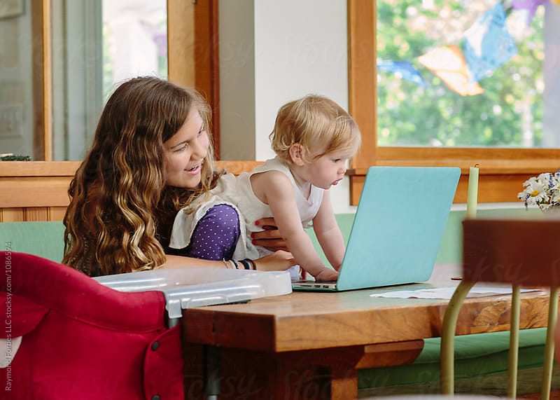 Teen Girl with Toddler Playing on Laptop by Raymond Forbes LLC for Stocksy United