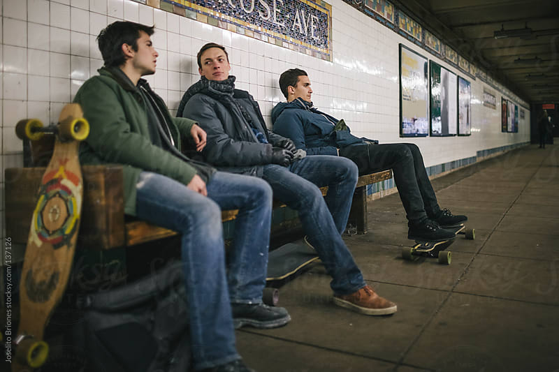 Young Men Friends Waiting for Train in New York Subway Station by Joselito Briones for Stocksy United