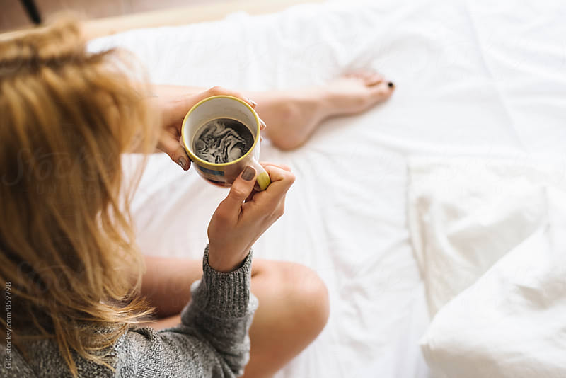 Woman holding a coffee mug in the bed by GIC for Stocksy United