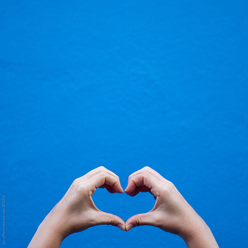 Love sign made by hands against a blue wall by Luca Pierro for Stocksy United